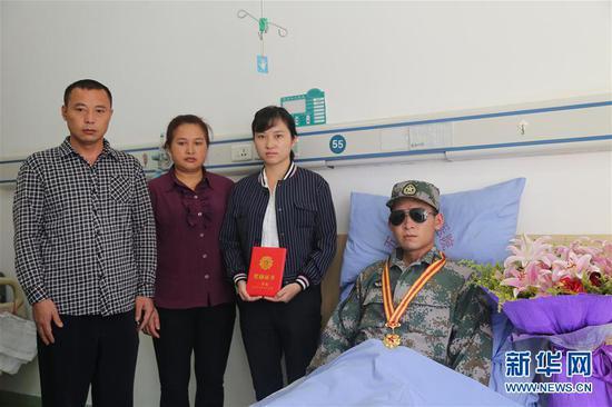 南部战区陆军云南扫雷大队在病房内为杜富国举行颁授一等功证书证章仪式后,杜富国与家人合影(11月24日摄)。