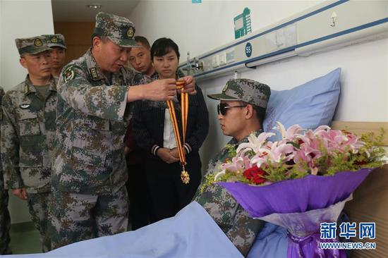 南部战区陆军云南扫雷大队在病房内为杜富国举行颁授一等功证书证章仪式,大队领导为他佩戴军功章(11月24日摄)。
