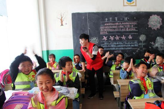 中铁二十局五公司的志愿者教同学们唱英文歌曲