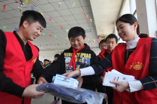 志愿者给学生发放学习用品