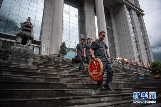 贡山县人民法院法官邓兴(右一)带着国徽前往乡间设立巡回法庭(8月31日摄)。新华社记者 江文耀 摄