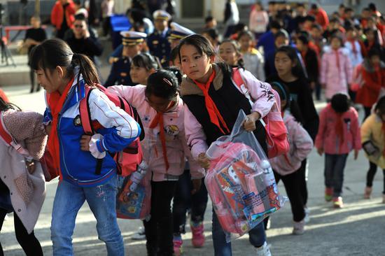 孩子们完成期末考试,手提新的学习用品,迎接新学期。摄影/马开龙