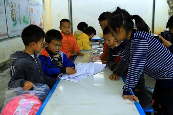 受捐助学生喜滋滋地与同学们分享绘画本。摄影/马开龙