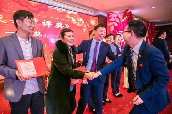 云瑞物业董事长简国帅在给员工颁奖