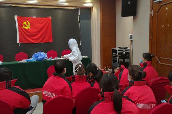 正在进行穿隔离衣训练的援鄂医疗队员。(云南援鄂医疗队供图)