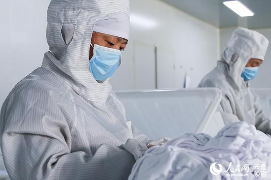 昆明康业医疗器械有限公司的员工正在车间内包装普通医用口罩。(人民网 李发兴 摄)