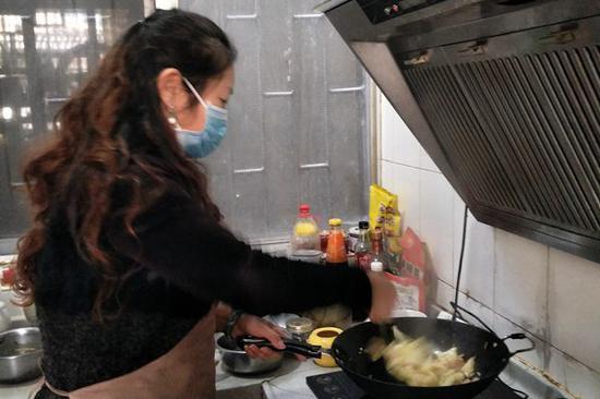 杨秋花在给家人做饭。(供图)