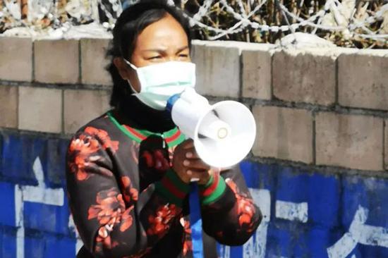 杨娜举着喇叭在村里宣传疫情防控知识。(供图)