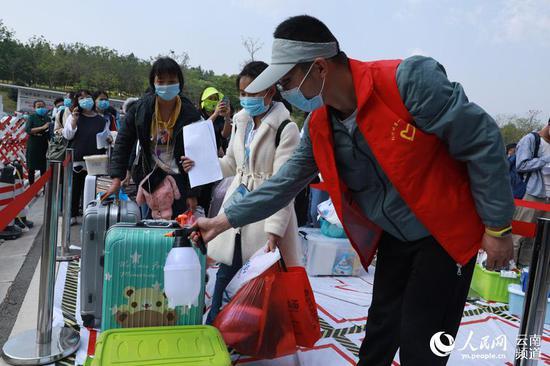 20日,红河州第一中学开学,入校前对报到学生的行李进行消毒。摄影:胡艳辉