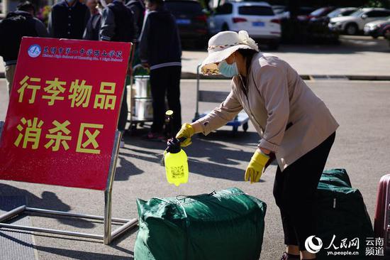 昆明市第一中学西山学校专门设置行李物品消杀区对学生行李进行消毒。摄影:王银行