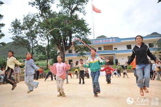 """文山州西畴县扭扣希望小学开展""""六一""""文体活动,图为小朋友们在进行跳绳比赛。(熊平祥摄)"""
