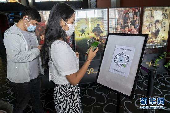 7月20日,观众在昆明市北辰财富中心影院入口处扫健康码。新华社发(陈欣波 摄)
