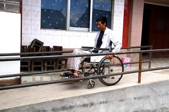 自从家里有了无障碍通道,罗信出行相对方便了。(程浩 摄)