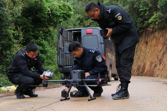 民警正在为无人机更换电池、做航前检查