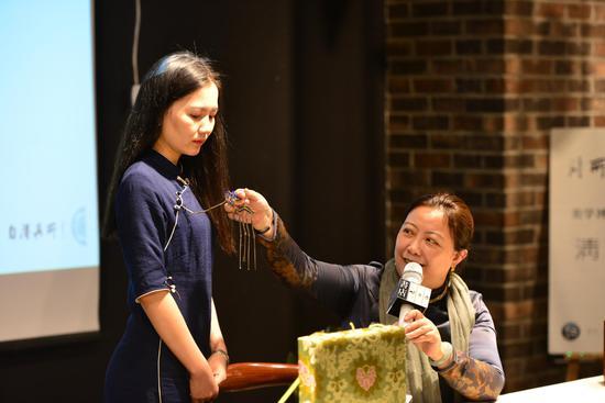 王玫梅向观众展示清中期的吉庆有余老银烧蓝压襟