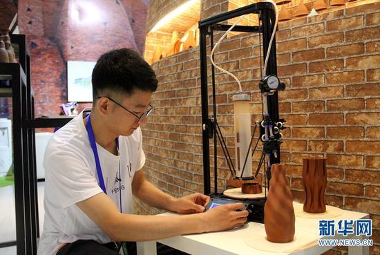 南博会旅游馆,胡竞正在操作他的3D打印机。 念新洪 摄