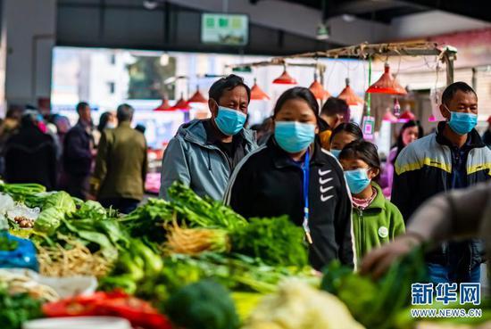 石元顺(左一)带着孩子们在农贸市场购买蔬菜(2月10日摄)。