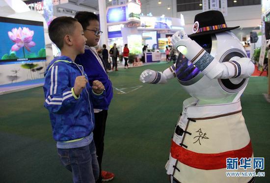 """南博会旅游馆,机器人导游""""小丽江""""在和逛展小朋友互动。念新洪 摄"""