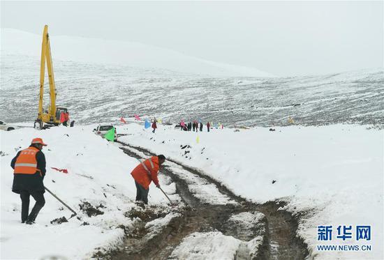 西藏道路抢通人员在西藏昌都市江达县海拔4500米左右的高山牧场上抢通道路(10月14日摄)。
