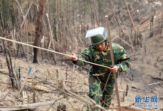 杜富国(右)与战友艾岩进行搜排作业(4月9日摄)。