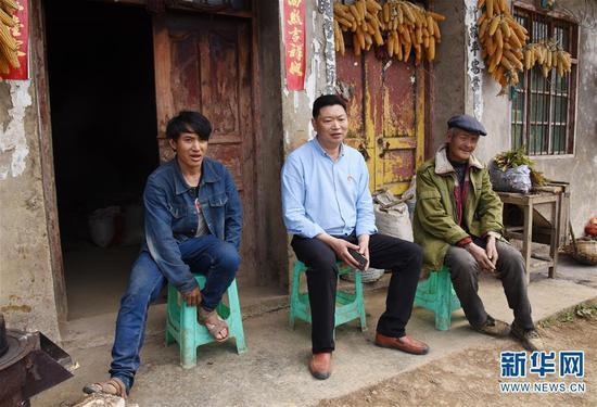 丁琪(中)在贫困群众家里动员他们开展黄牛养殖