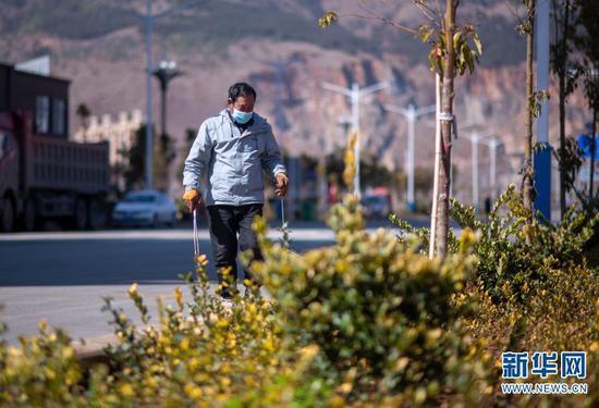 石元顺在安置小区打扫卫生(2月10日摄)。