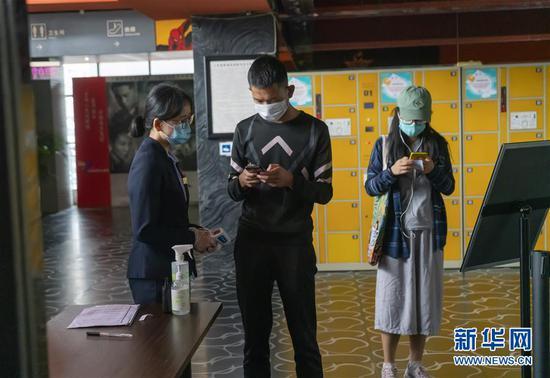 7月20日,在昆明市北辰财富中心影院入口处,工作人员指导观众填写防疫信息。新华社发(陈欣波 摄)