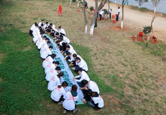 参与植树人员在活动布标上写下祝福语并签字留影