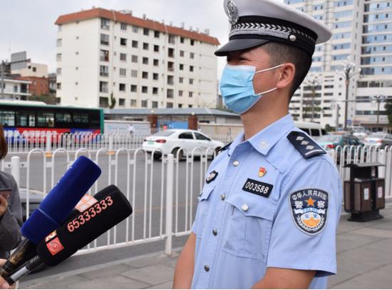昆明市交警一大队六中队民警杨峰在活动现场接受采访