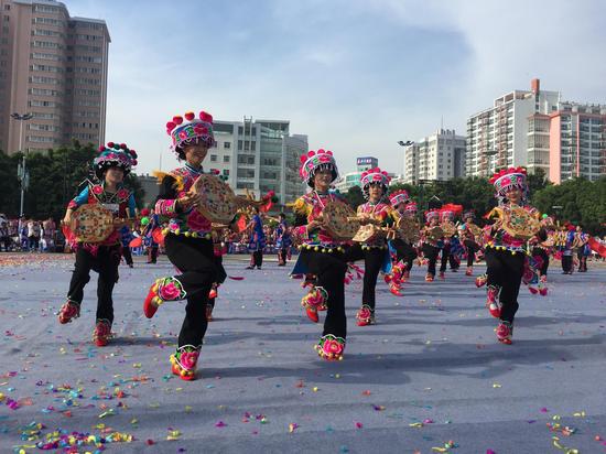 (身着彝族服饰的姑娘跳着欢快的彝族歌舞)
