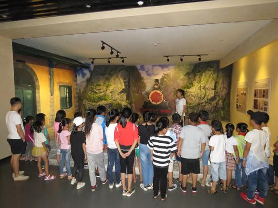 ▲参观文博馆的同学们正聚精会神地听讲解员在讲解建水的历史文化
