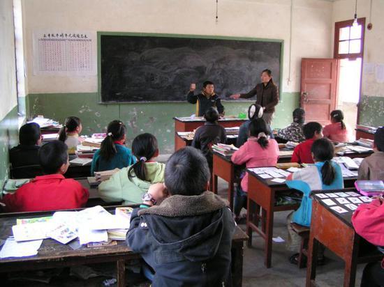 志愿者韩琦给云南小学生上英语课,台上举着音标卡的正是五年级的和超。