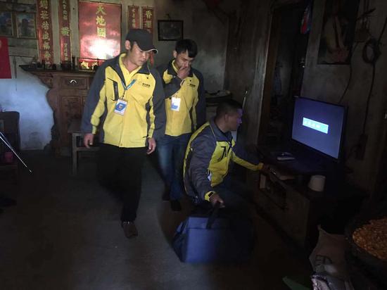(图:苏宁工作人员在为农户安装电视)