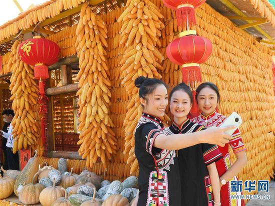 2月8日,身着民族服饰的女孩在澜沧拉祜族自治县民族团结进步广场的玉米房前拍照留念。 新华社记者杨宗友摄