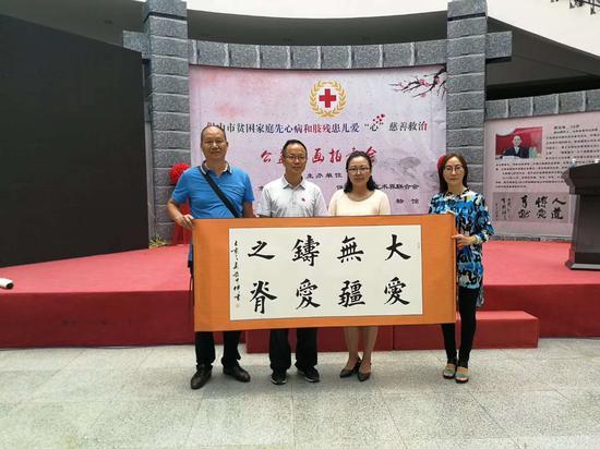 企业家董荣富(左一)拍下作品《大爱无疆 铸爱之脊》赠与保山市红十字会