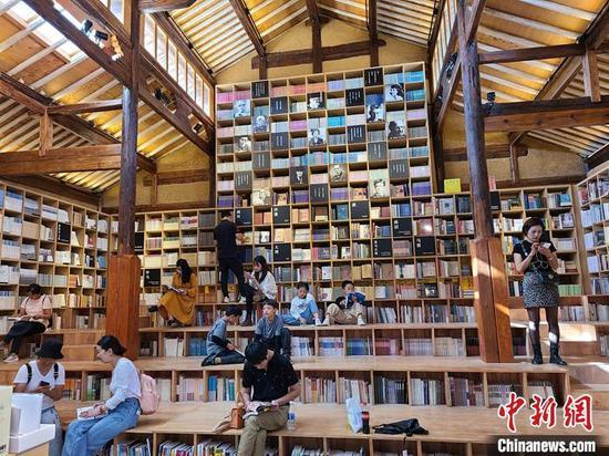 10月4日,游客在先锋沙溪白族书局内阅览书籍。 中新社记者 韩帅南 摄