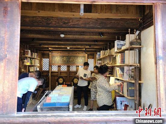 10月5日,游客在沙溪古镇了解马帮文化。 中新社记者 韩帅南 摄