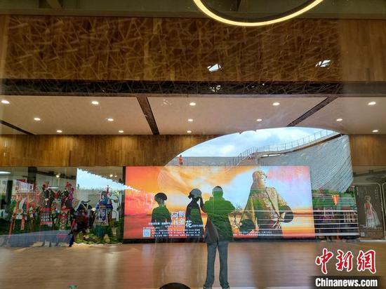 10月6日,一位游客在杨丽萍大剧院的灯牌前拍照留念。中新社记者 韩帅南 摄