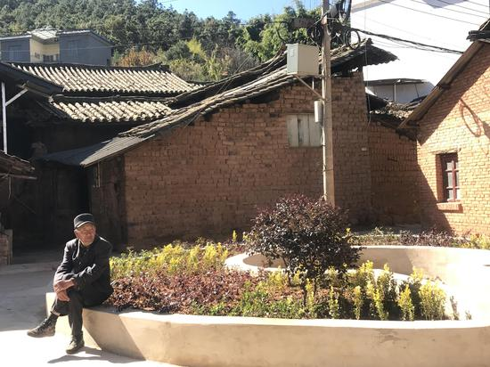 田冲小组村民正在改造后的小广场晒太阳