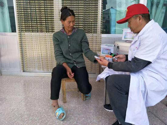 """""""云南省五一劳动奖章""""获得者杨品一在给群众量血压"""