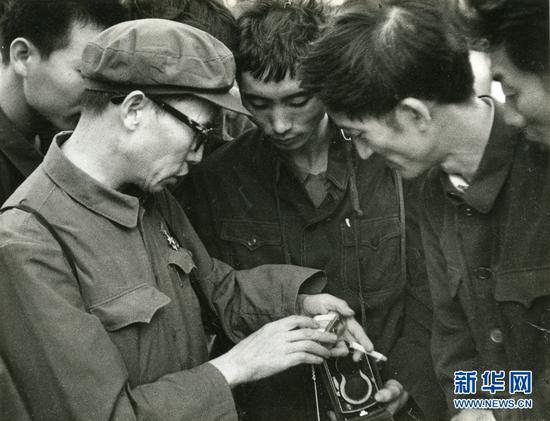 1969年,杨长福(左1)在和摄友们交流。受访者供图