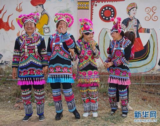 (在永仁县晓丽绣品专业合作社,彝族绣女们穿着彝族服饰合影留念,她们在镜头前有些害羞)
