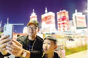 家住世纪城的李先生一家,刚走出东风广场地铁站就被美景留住脚步,拿出手机合影留念。