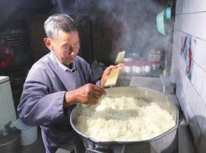 高家恩老人在 专门的厨房里蒸糯米