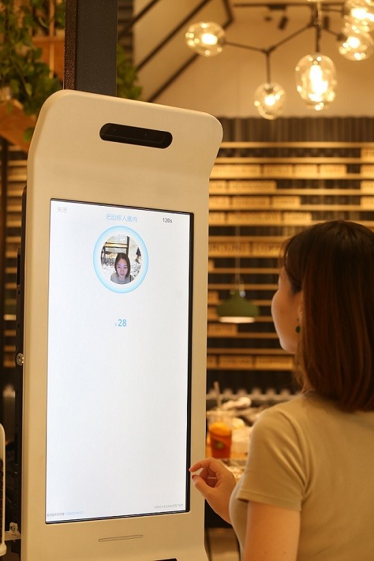 一名顾客在餐厅使用Smile to Pay刷脸支付功能支付餐费