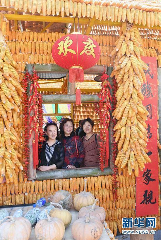 2月8日,游客在澜沧拉祜族自治县民族团结进步广场的玉米房内拍照留念。 新华社记者杨宗友摄