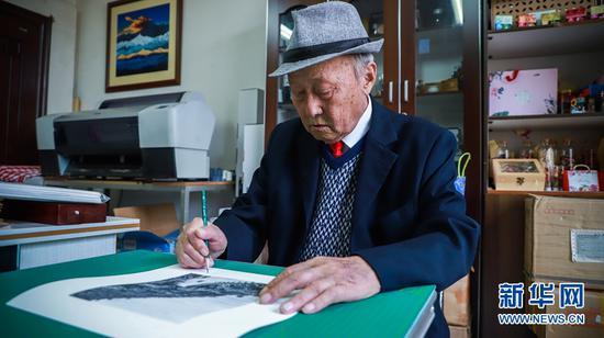"""杨长福拍摄的老照片广受市民喜爱,图为老人在照片下为""""粉丝""""签名。新华网 周亚平 摄"""