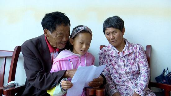 饶学玉的父母正在听孙女朗读《三字经》