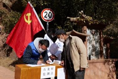 沙溪镇石龙村驻村工作队员为村民测量体温后登记