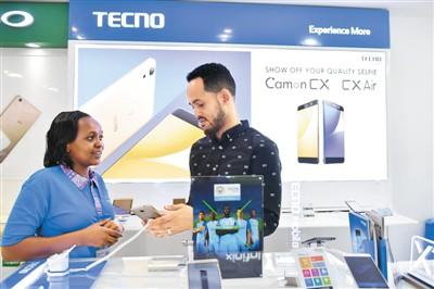 在肯尼亚首都内罗毕市中心一家手机店,销售人员向顾客介绍中国深圳一家手机厂商生产的传音手机(2017年5月9日摄)。新华社记者 孙瑞博摄